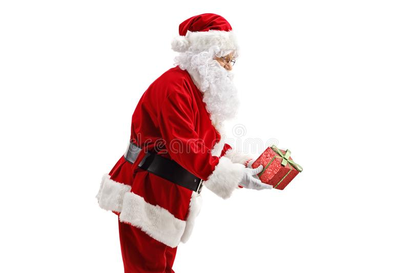 Profile of Santa Claus giving a present stock photography