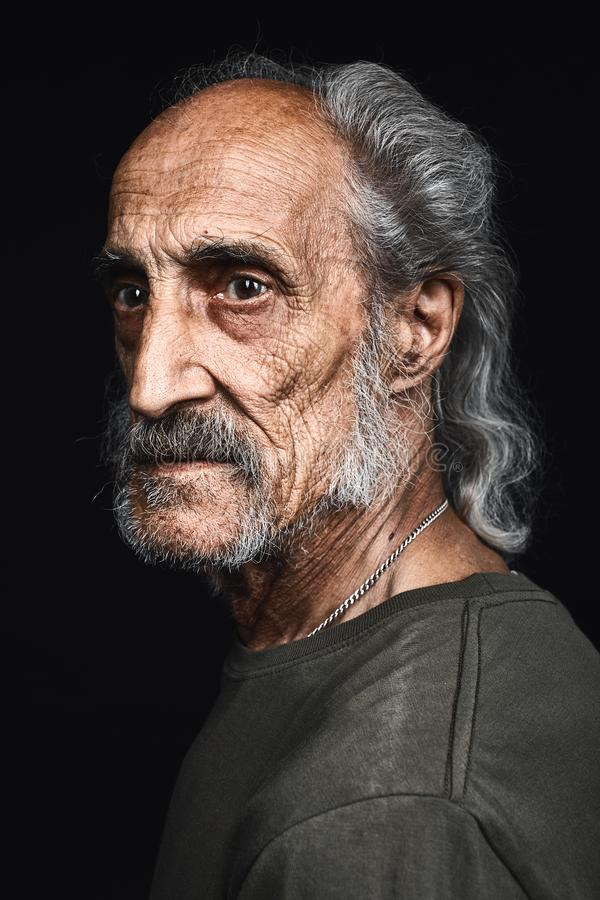 Profile of senior man with gray hair and bold with serious expression stock image