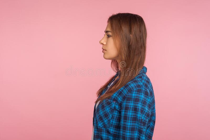 Profile of serious unsmiling girl in checkered shirt looking to side copy space with calm attentive focused expression. Student or employee in casual outfit stock photos