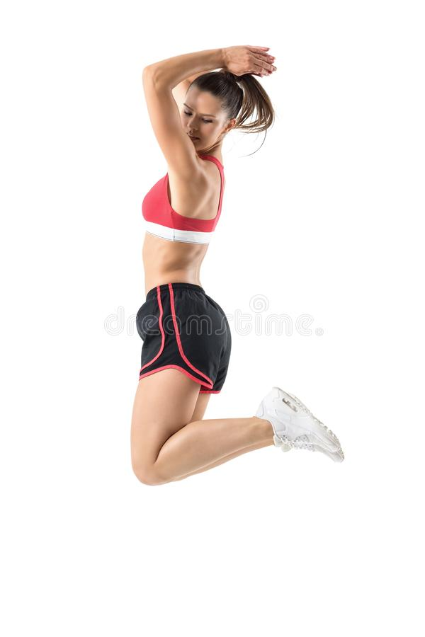 Profile of serious young fit sporty woman jumping in mid air looking back over shoulder. stock photo
