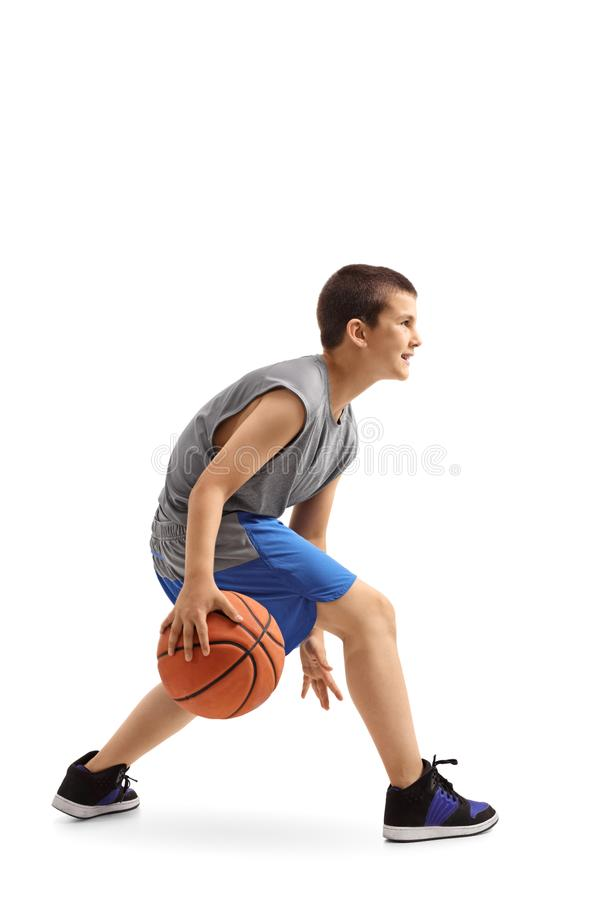 Profile shot of a boy dribbling a basketball. Isolated on white background stock photo