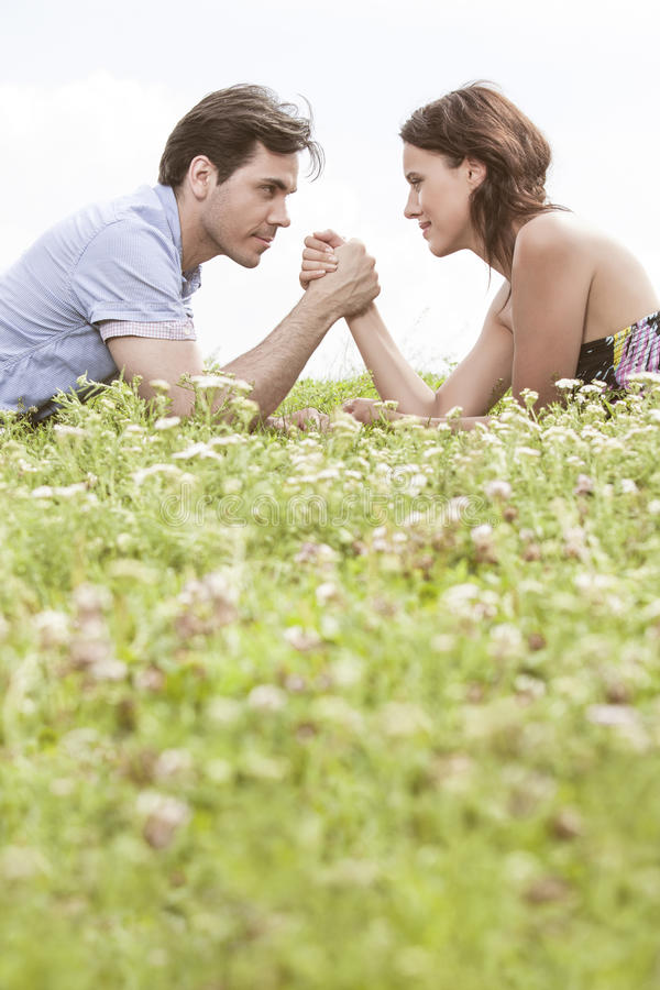Profile shot of couple arm wrestling while lying on grass against sky royalty free stock photo