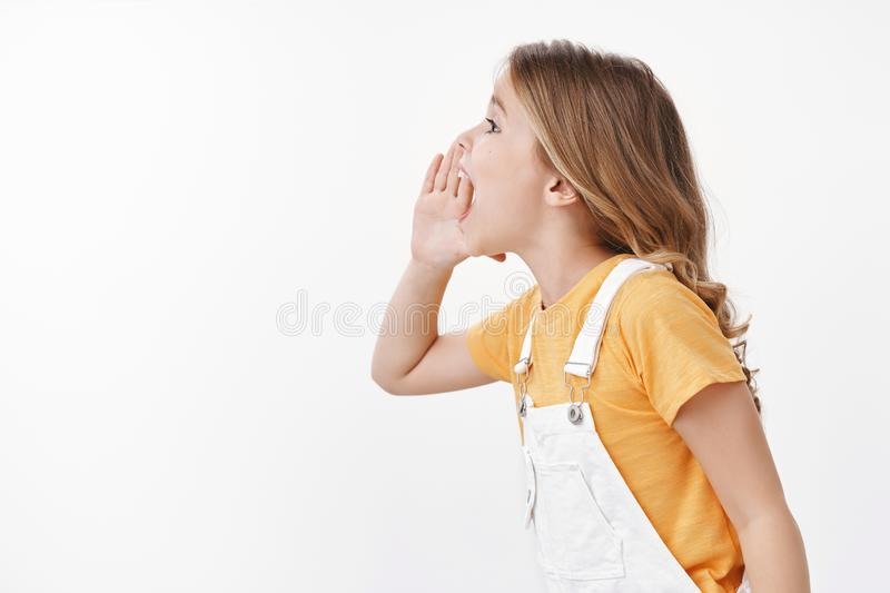 Profile shot energized playful cute charismatic little girl, child calling friend, shouting hold hand near opened mouth royalty free stock photography