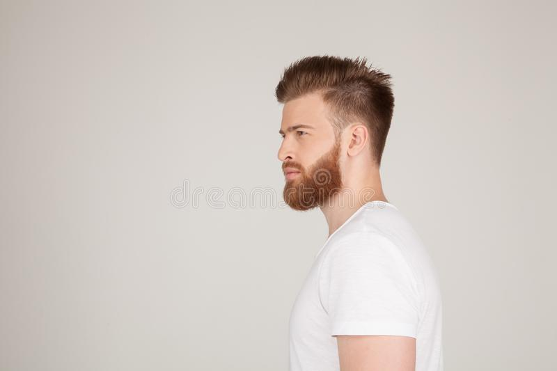 Profile shot of handsome male with trendy hairdo and beard, looks aside with serious expression, has thick red beard, isolated stock images