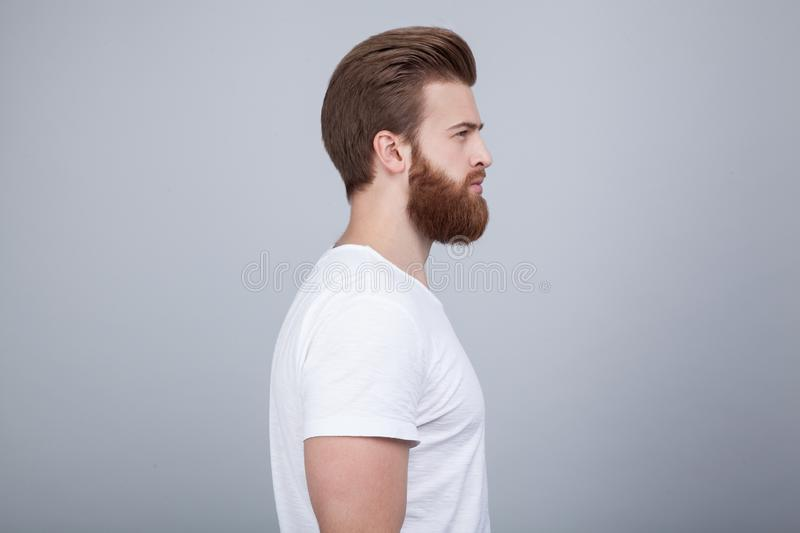Profile shot of handsome male with trendy hairdo and beard, looks aside with serious expression, has thick red beard, stock images