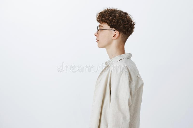 Profile shot of stylish handsome young hipster male freelancer with curly hairstyle in glasses looking left and standing royalty free stock image