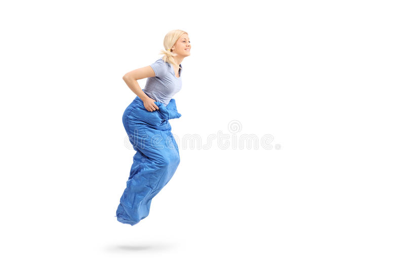 Profile shot of a young blond woman sack jumping royalty free stock images