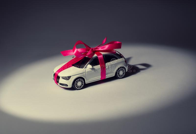 Profile side close up view photo of toy white car wrapped in cut stock image