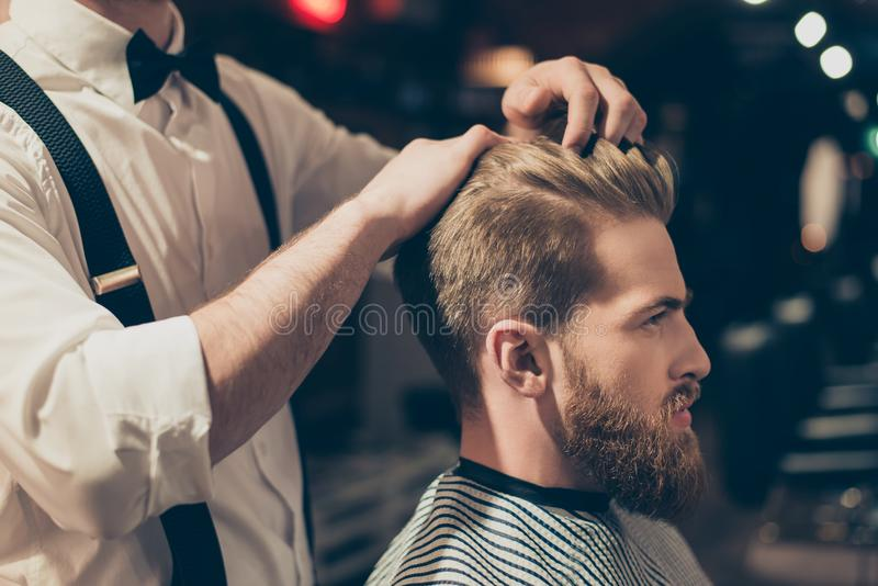 Profile side close up view portrait of handsome virile macho man having his hair cut in barbershop. Fashion hair care concept. Bea stock images