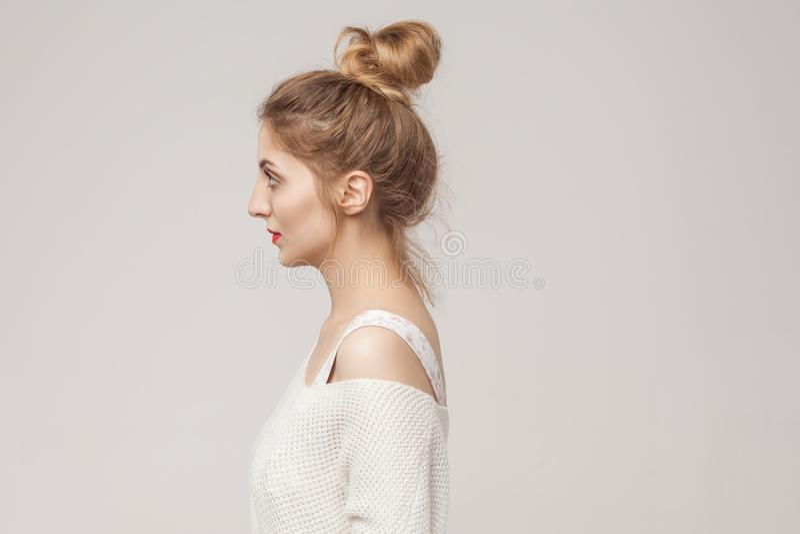 Profile side mixed race blonde woman looking away. Studio shot stock photography