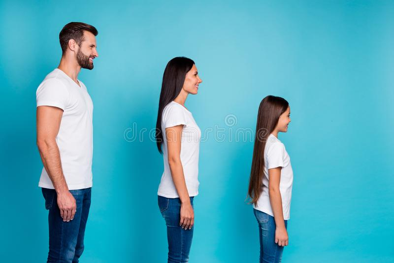 Profile side photo of charming people standing isolated wearing white t-shirt denim jeans over blue background royalty free stock photography