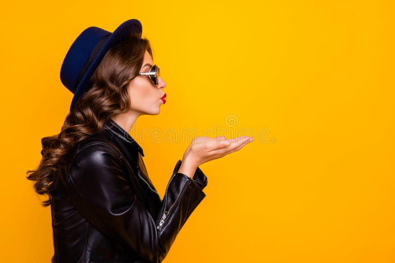 Profile side photo of dream dreamy girl send air kises to her boyfriends on 14-february date wear modern black leather. Jacket isolated, over yellow color royalty free stock image