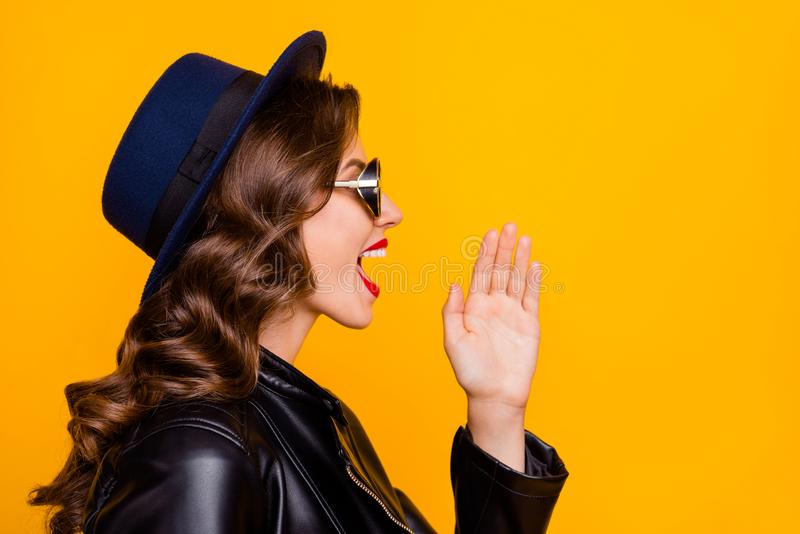 Profile side photo of funky fun girl scream ads private novelties say tell sales discounts wear black leather jacket. Isolated over yellow, background stock photos