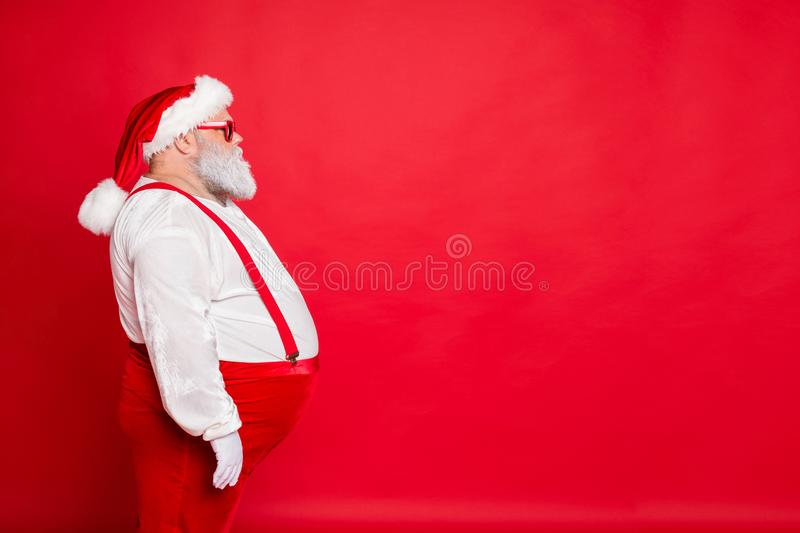 Profile side photo of white gray hair fat overweight santa claus with big funny belly abdomen ready for new year. Profile side photo of white gray hair fat royalty free stock photo