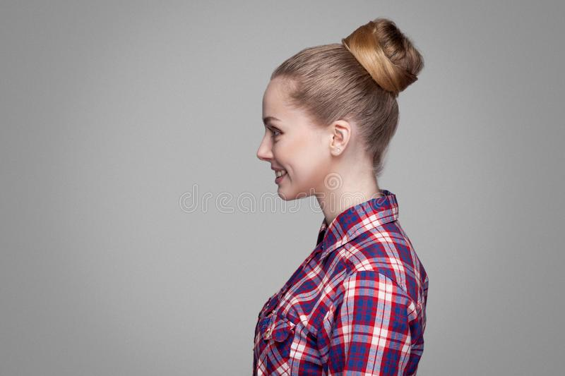 Profile side view of beautiful blonde girl in red, pink checkered shirt, collected bun hairstyle standing and looking aside with royalty free stock image
