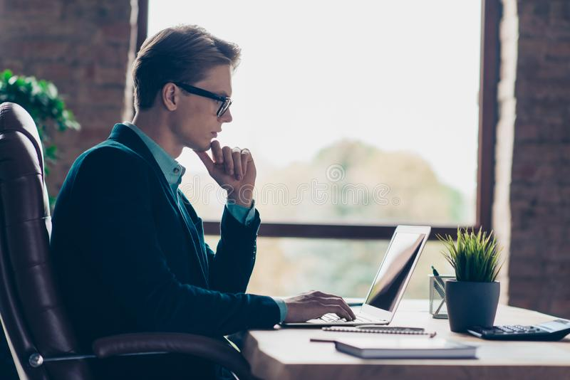 Profile side view photo focused pensive collar touch chin thoughtful ponder look develop start-up marketing document. True specialist suit black jacket sit desk stock image