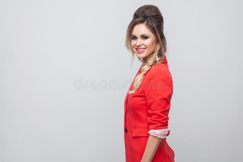 Profile side view portrait of beautiful happy business lady with hairstyle and makeup in red fancy blazer standing and looking at. Camera with toothy smile royalty free stock photos