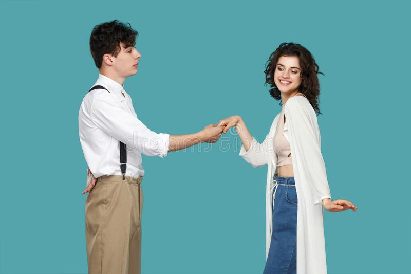 Profile side view portrait of brunette stylish gentleman standing and holding hand of cheerful happy young woman with toothy smile royalty free stock images