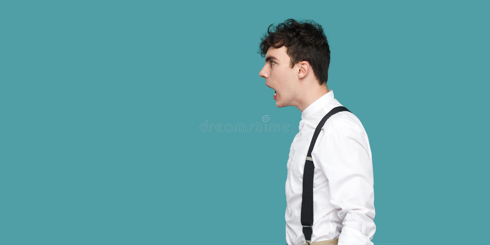 Profile side view portrait of crazy or shocked handsome hipster curly young businessman in classic casual white shirt and stock photos