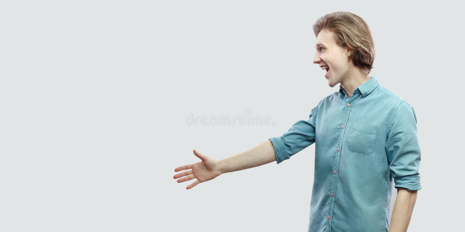 Profile side view portrait of excited happy handsome long haired blonde young man in blue casual shirt standing and giving hand ot stock photos
