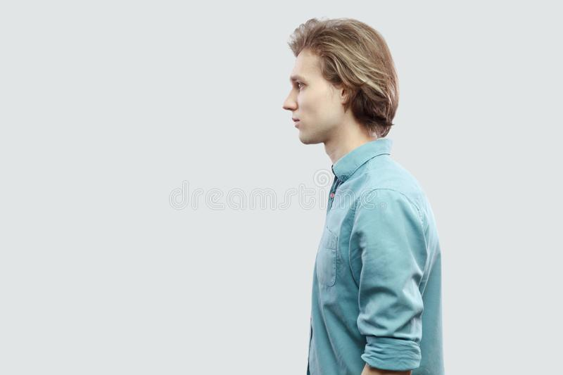 Profile side view portrait of handsome long haired blonde young man in blue casual shirt standing and looking with serious face stock images