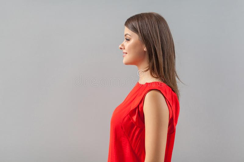 Profile side view portrait of happy beautiful brunette young woman in red shirt standing and looking forward with toothy smile and stock photos