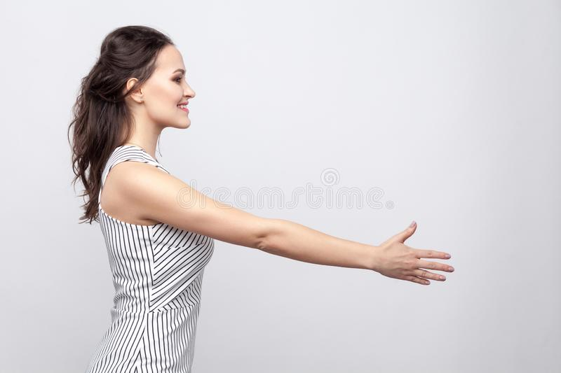 Profile side view portrait of happy beautiful young brunette woman with makeup and striped dress standing and giving hand to stock images