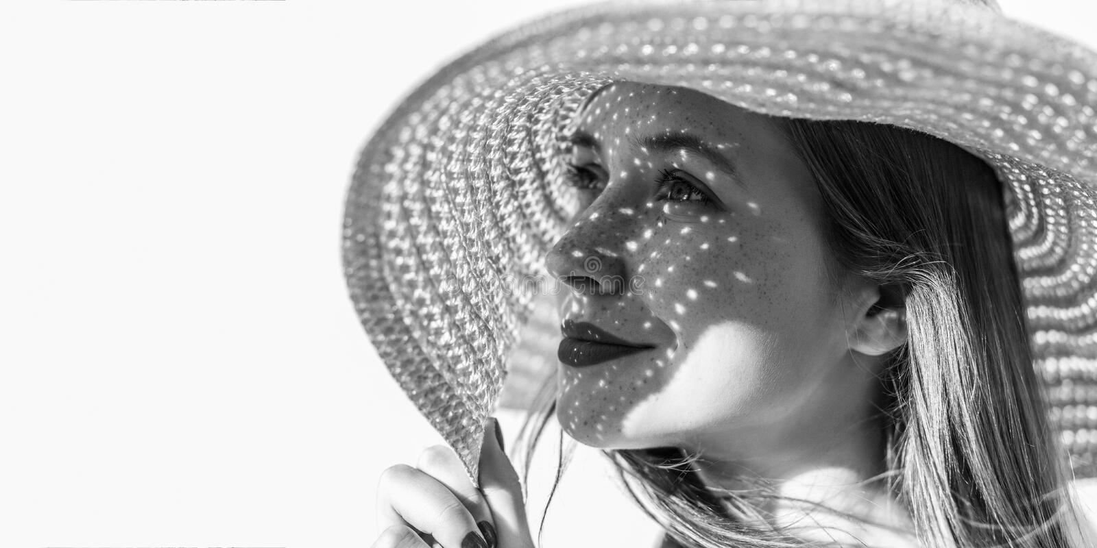 Profile side view portrait of happy dreamy beautiful young woman with hat looking away and smiling, holding hat, light through hat royalty free stock images