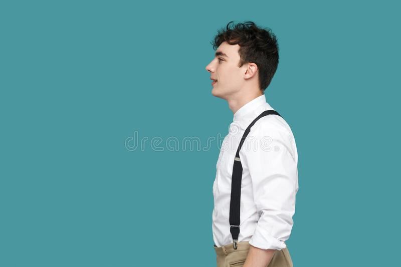 Profile side view portrait of happy handsome hipster curly young businessman in classic casual white shirt and suspender standing royalty free stock images