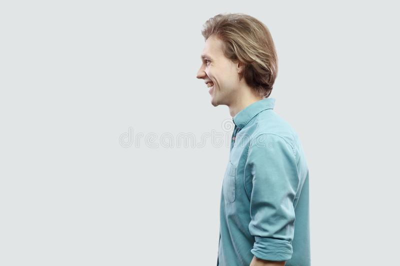 Profile side view portrait of happy handsome long haired blonde young man in blue casual shirt standing and looking with toothy royalty free stock images