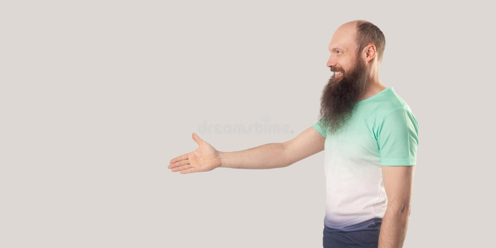 Profile side view portrait of happy satisfied bald bearded man in t-shirt standing, giving hand ro greeting or handshake and. Looking with toothy smile. indoor royalty free stock images
