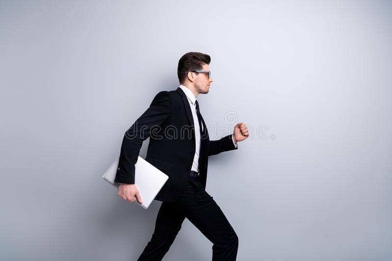 Profile side view portrait of nice chic attractive content guy carrying in hands laptop marketing manager executive royalty free stock image