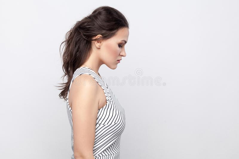 Profile side view portrait of sad beautiful young brunette woman with makeup and striped dress standing holding head down with stock image