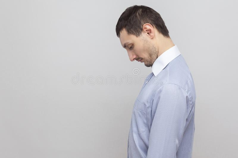 Profile side view portrait of sad depressed handsome bristle businessman in classic blue shirt standing holding head down and royalty free stock photography