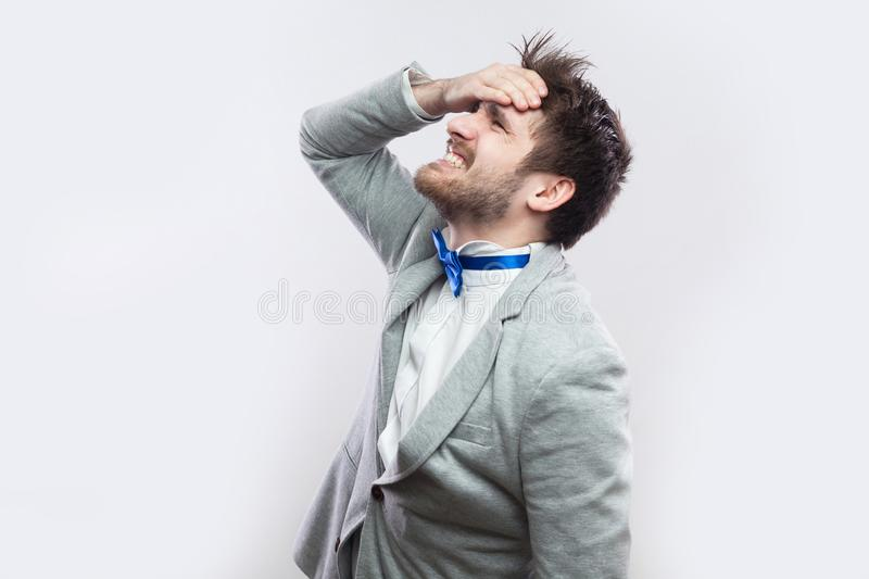 Profile side view portrait of sad handsome bearded man in casual grey suit and blue bow tie standing hopeless because he lose royalty free stock photography