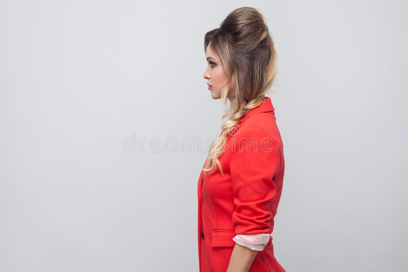 Profile side view portrait of serious beautiful business lady with hairstyle and makeup in red fancy blazer, standing and looking. Straight. indoor studio shot royalty free stock photo