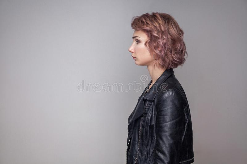 Profile side view portrait of serious beautiful girl with short hairstyle and makeup in casual style black leather jacket standing stock photos