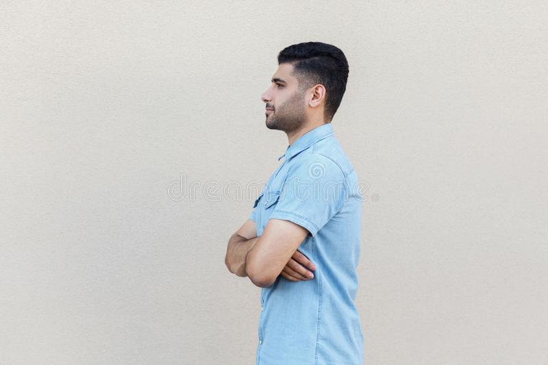 Profile side view portrait of serious calm handsome young bearded man in blue shirt standing, crossed arms and looking forward royalty free stock images
