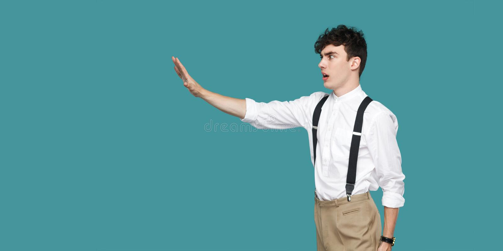 Profile side view portrait of serious handsome hipster curly young businessman in classic casual white shirt and suspender royalty free stock images