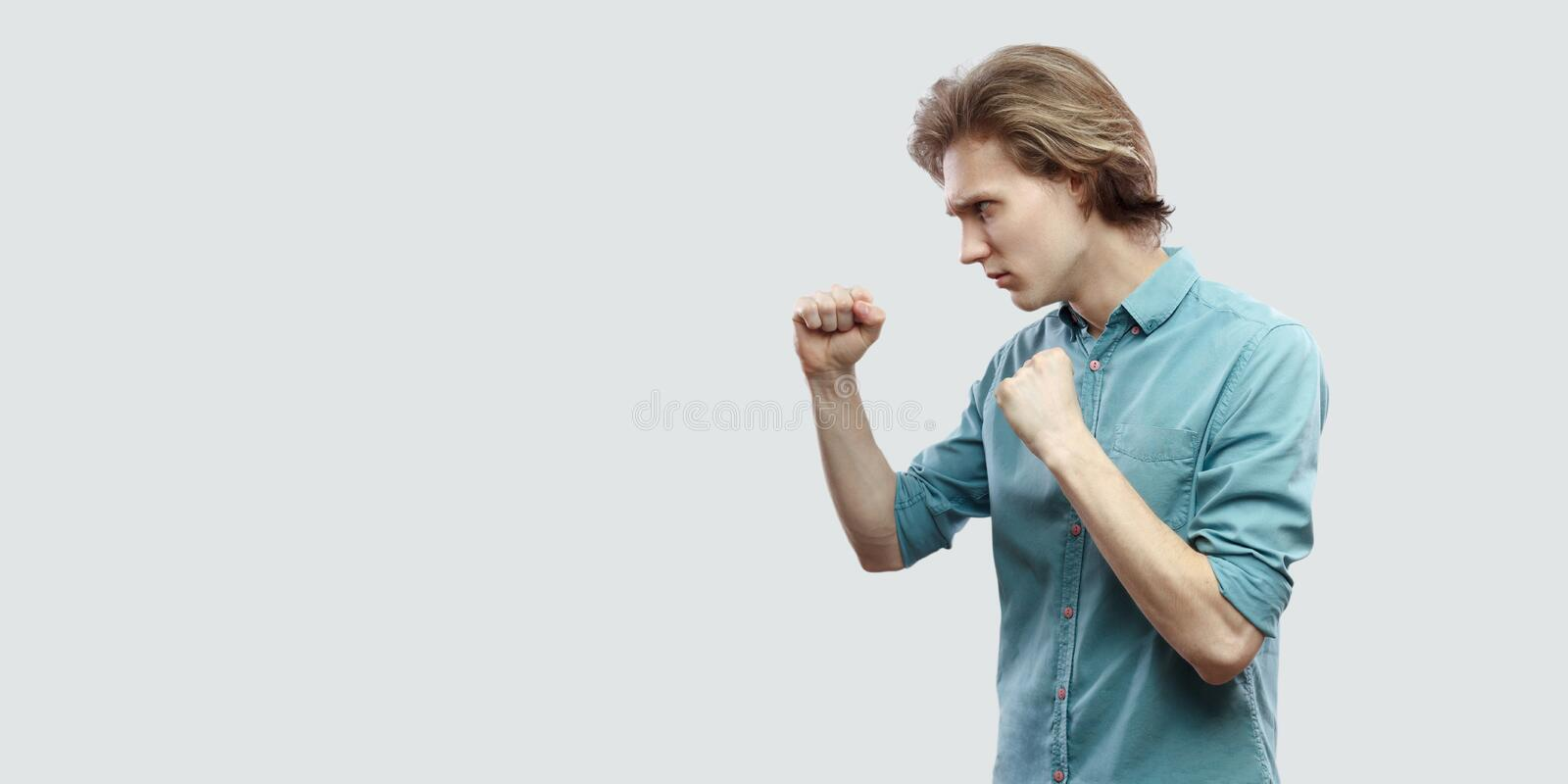 Profile side view portrait of serious handsome long haired blonde young man in blue casual shirt standing with boxing gesture and. Ready to attack. indoor stock image