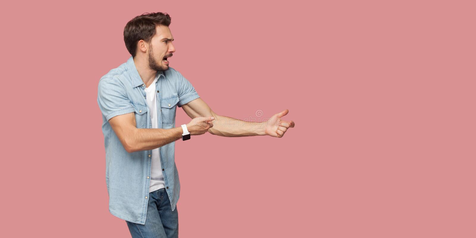 Profile side view portrait of serious screaming bearded young man in blue casual shirt standing in attack or pulling hands gesture stock image