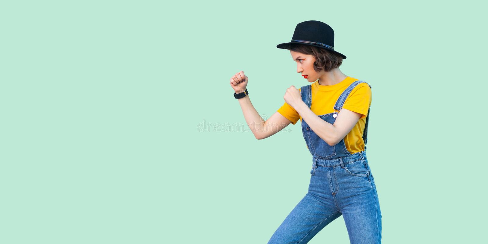 Profile side view portrait of serious young girl in blue denim overalls, yellow shirt, black hat standing with boxing fists and. Ready to attack. indoor studio stock photos