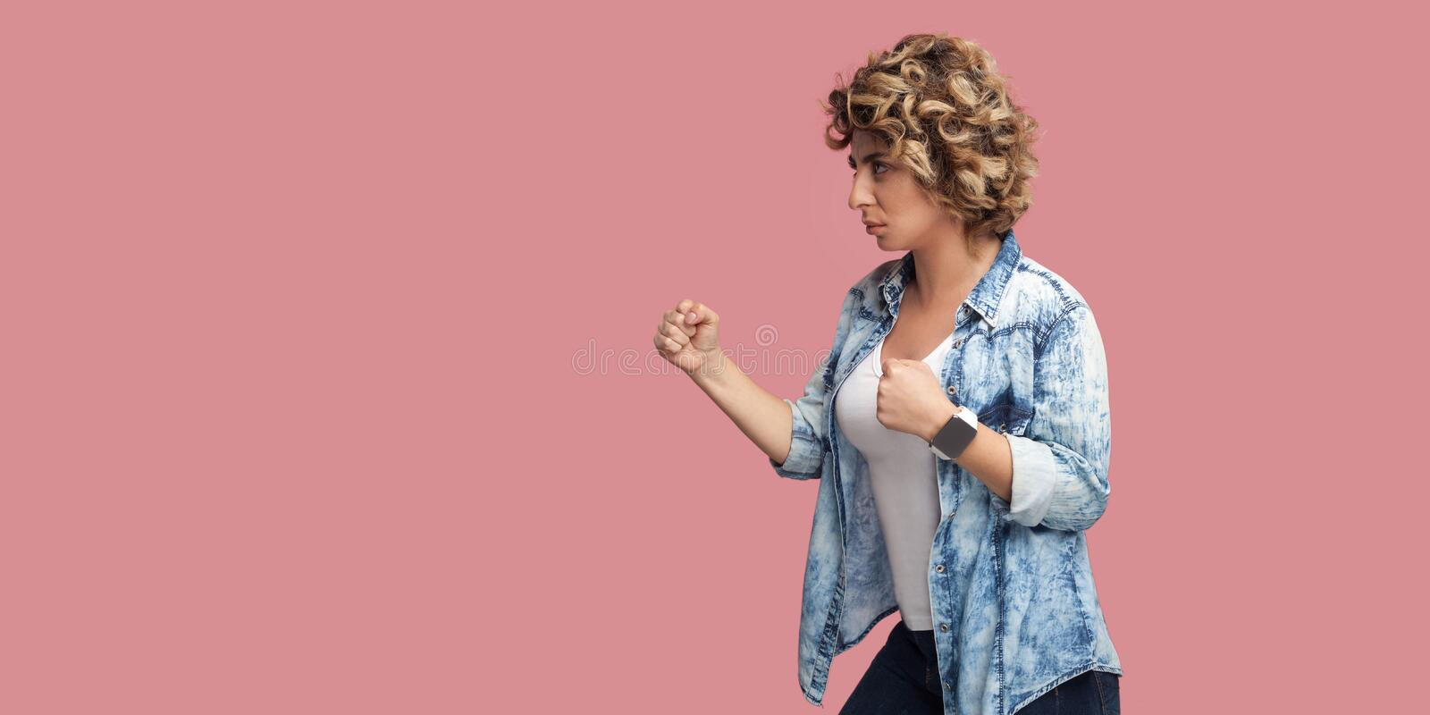 Profile side view portrait of serious young woman with curly hairstyle in casual blue shirt standing with boxing fists, looking. Forward, ready to attack stock image