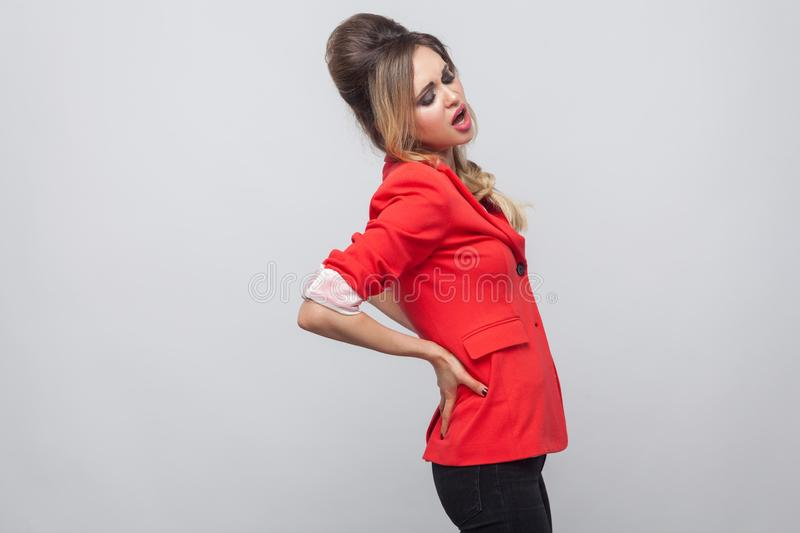 Profile side view portrait of tired beautiful business lady with hairstyle and makeup in red fancy blazer, standing and feeling. Pain on her spine. indoor royalty free stock image