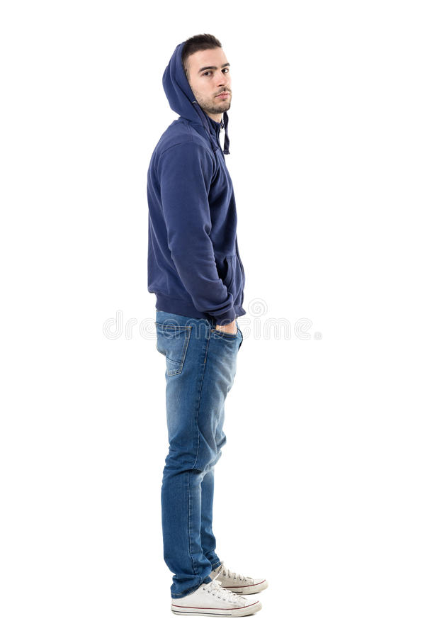 Profile of tough young casual man in blue hoodie looking intense at camera. Full body length portrait isolated over white studio background stock images
