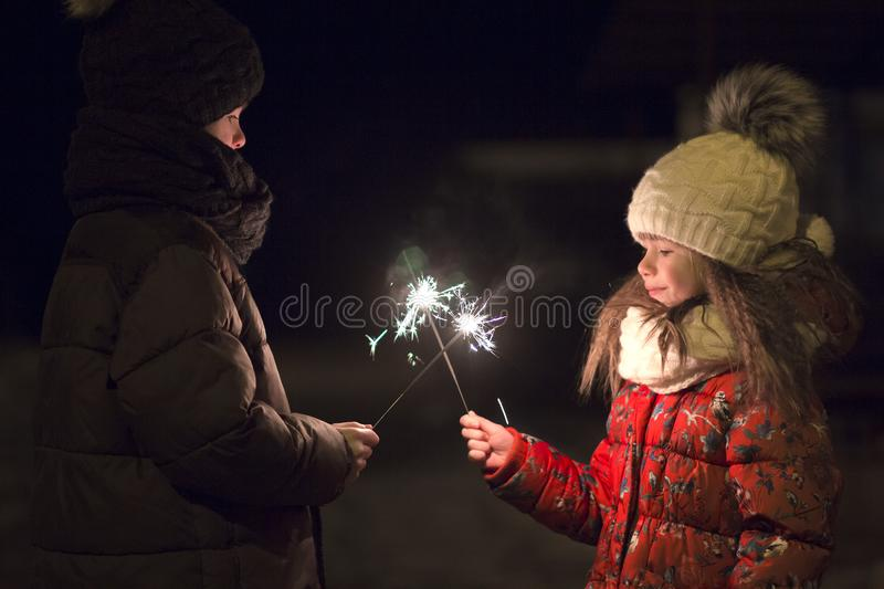 Profile of two cute young children, boy and girl in warm winter clothing holding burning sparkler fireworks on dark night outdoors royalty free stock image