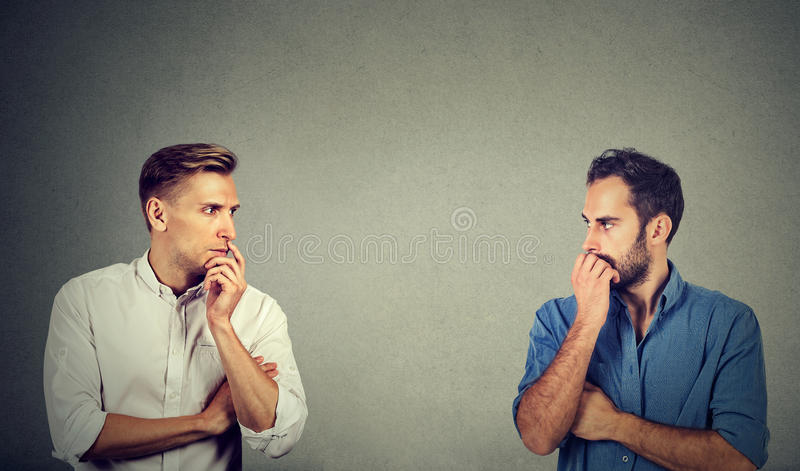 Profile of two preoccupied businessmen looking at each other royalty free stock image