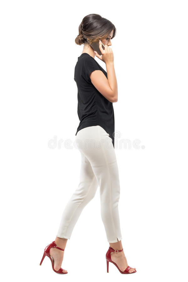 Profile view of busy business woman employee walking and talking on the phone looking down. royalty free stock images