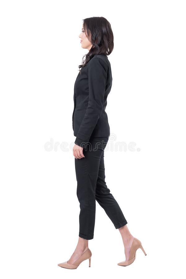 Profile view of elegant business woman in suit stepping forward. Full body isolated on white background royalty free stock photos