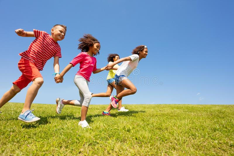 Diverse group of happy kids run in park hold hands royalty free stock photo